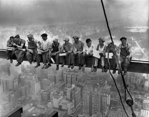 Men seated on construction beam, eating lunch.